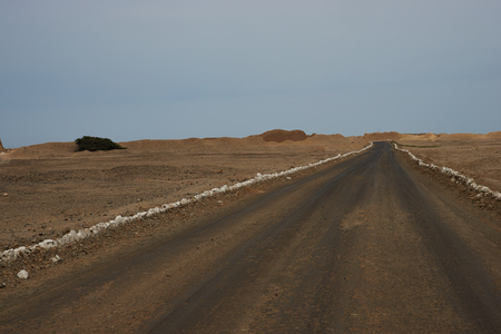 apogee: Gravel road leading to the remains of the historic city of Chan Chan near Trujillo in Peru. The city was the capital of the Chimu Kingdom which reached its apogee in the 15th Century. It is a UNESCO World Heritage Site. Stock Photo