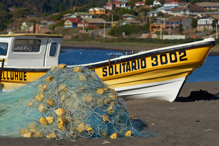Curanipe, Chile - April 21, 2015: Colourful fishing boat and fishing nets on the beach in the small fishing village of Curanipe in the Maule Region of Chile.