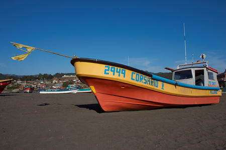 Curanipe, Chile - April 21, 2015: Colourful fishing boat on the beach in the small fishing village of Curanipe in the Maule Region of Chile.