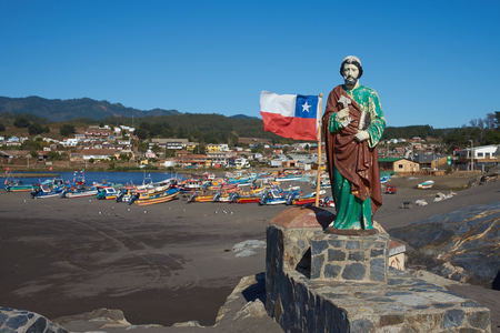colourfully: Colourfully painted statue of Saint Peter along side the flag of Chile on a rocky promontory sheltering the beach used by the fishing fleet in the small fishing village of Curanipe in the Maule Region of Chile. Fishing boats beyond. Stock Photo
