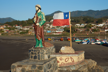 fishing fleet: Colourfully painted statue of Saint Peter along side the flag of Chile on a rocky promontory sheltering the beach used by the fishing fleet in the small fishing village of Curanipe in the Maule Region of Chile. Fishing boats beyond. Stock Photo