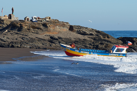 beached: Curanipe Chile  April 22 2015: Fishing boat coming ashore on the sandy beach in the fishing village of Curanipe Chile. Once the boats are beached on the sand a tractor is used to pull the boats to safer ground.