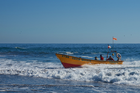 Curanipe Chile  April 22 2015: Fishing boat coming ashore on the sandy beach in the fishing village of Curanipe Chile. Once the boats are beached on the sand a tractor is used to pull the boats to safer ground.