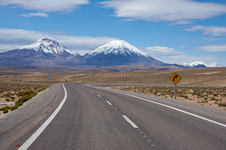 ice covered: Road running towards the snow and ice covered peaks of the volcanoes Parinacota 6342m and Pomerape 6240m rising above the Altiplano of Northern Chile in Lauca National Park.