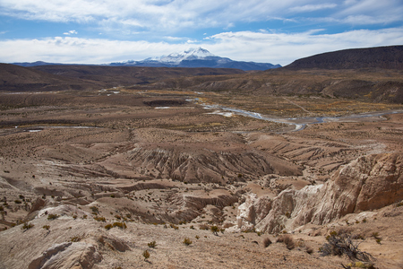 Eroded rock formations at the head of a river valley feeding the River Lauca high up on the Altiplano of northern Chile in Lauca National Park.  In the background is the snow capped active Guallatiri volcano 6063 m. Stock Photo