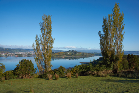 sheltered: Castro, the capital of Chiloe Island in Chile. Small city located in a rural setting on the far side of a sheltered inlet.