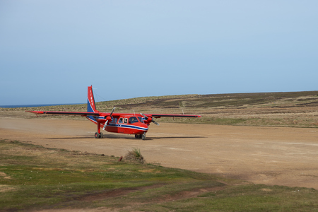 aircraft landing: FALKLAND ISLANDS, OCTOBER 28, 2015: Small aircraft landing on a gravel airstrip on Sealion Island in the Falkland Islands