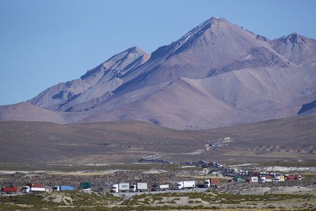 americal: LAUCA NATIONAL PARK, CHILE - MAY 11, 2016: Long line of trucks waiting on the altiplano of northern Chile to cross into Bolivia. Editorial