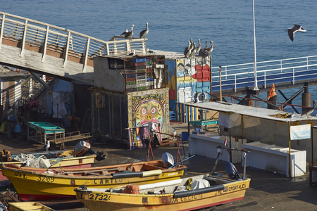 inshore: VALPARAISO, CHILE - JULY 5, 2016: Colourful inshore fishing boats on the quayside at the fish market