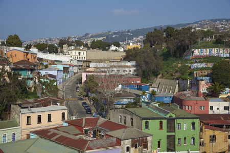 colourfully: VALPARAISO, CHILE - JULY 5, 2016: Colourfully decorated houses crowd the hillsides below a historic cemetery of the historic port city of Valparaiso in Chile. Editorial