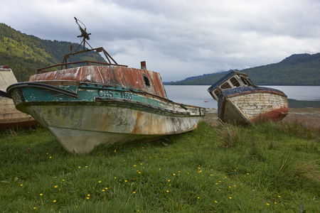 chilean: Abandoned and neglected fishing boat drawn up on the beach at Puyuhuapi along the Carretera Austral in Chilean Patagonia. Stock Photo