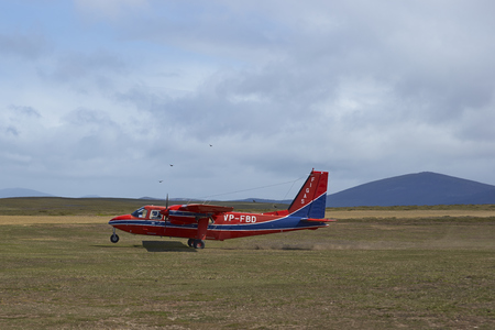airstrip: FALKLAND ISLANDS, OCTOBER 26, 2016: Small aircraft landing on a gravel airstrip on Saunders Island in the Falkland Islands