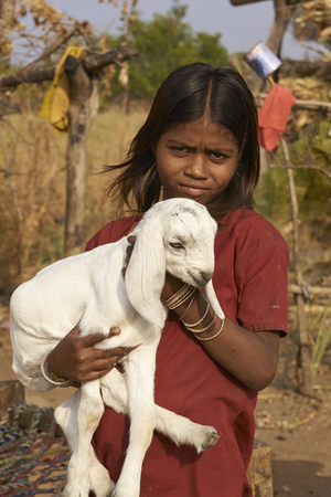 madhya: MANDU, MADHYA PRADESH, INDIA - NOVEMBER 19, 2008: Young girl holding a small kid goat in the rural hilltop fortress of Mandu in Madhya Pradesh, India Editorial