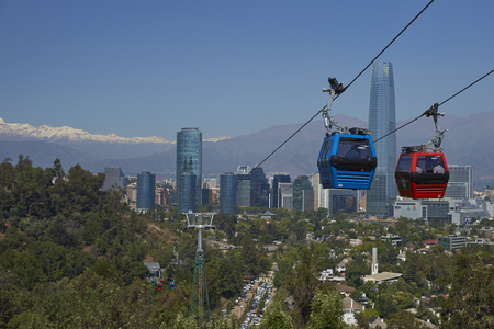 cristobal: SANTIAGO, CHILE - DECEMBER 27, 2016: Cable car on Cerro San Cristobal in Santiago, Chile.  Beyond, modern skyscrapers of the Las Condes area of the city and snow capped mountains of the Andes. Editorial