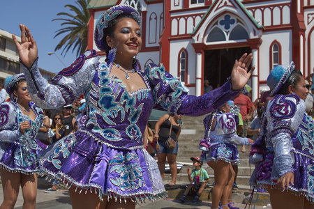 ARICA, CHILE - FEBRUARY 10, 2017: Female members of a Caporales dance group in ornate costumes performing at the annual Carnaval Andino con la Fuerza del Sol in Arica, Chile. Editorial