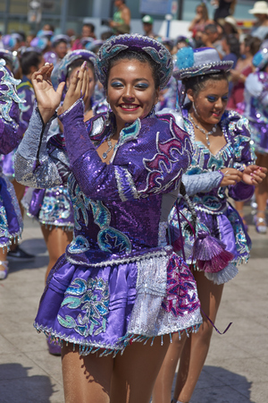 bolivian: ARICA, CHILE - FEBRUARY 10, 2017: Female members of a Caporales dance group in ornate costumes performing at the annual Carnaval Andino con la Fuerza del Sol in Arica, Chile. Editorial