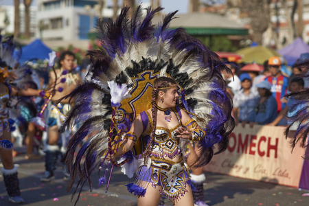 chilean: ARICA, CHILE - FEBRUARY 10, 2017: Female member of a Tobas dance group in ornate costume performing at the annual Carnaval Andino con la Fuerza del Sol in Arica, Chile.