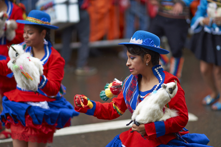 bolivian: ORURO, BOLIVIA - FEBRUARY 25, 2017: Llamerada dancers in ornate costumes performing as they parade through the mining city of Oruro on the Altiplano of Bolivia during the annual carnival.