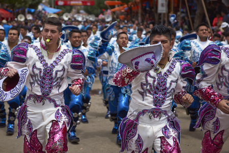 bolivian: ORURO, BOLIVIA - FEBRUARY 26, 2017: Caporales dancers in ornate costumes performing as they parade through the mining city of Oruro on the Altiplano of Bolivia during the annual carnival.