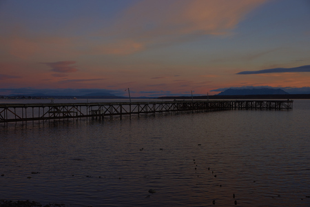 Sunset over the sea and mountains of Patagonia at Puerto Natales in southern Chile Imagens