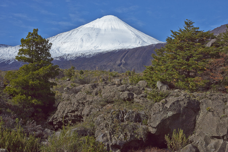 metres: Snow capped peak of Antuco Volcano (2,979 metres) rising above a forested valley in Laguna de Laja National Park in the Bio Bio region of Chile. Stock Photo