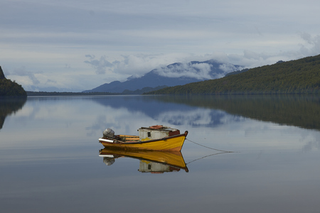 Puyuhuapi, Aysén Region, Chile - November 12, 2017: Small boat moored on the still waters of a sea loch at Puyuhuapi, a small town on the Carretera Austral in northern Patagonia, Chile. Editorial