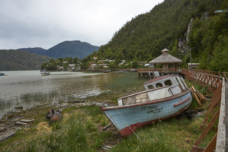 Tortel, Patagonia, Chile - November 16, 2017: Wooden fishing boat beached on the coast in the small village of Tortel in northern Patagonia, Chile.