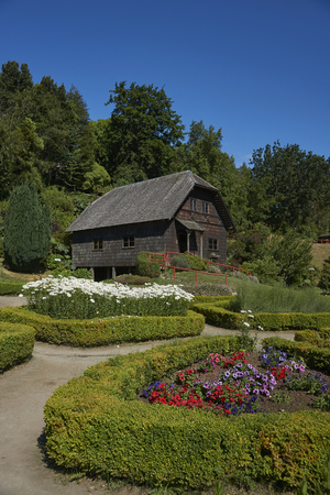 Frutillar, Los Largos, Chile - January 24, 2018:  Traditional wooden farm buildings set in the landscaped gardens of the German Colonial Museum in Frutillar in the Lake District of southern Chile. Editorial