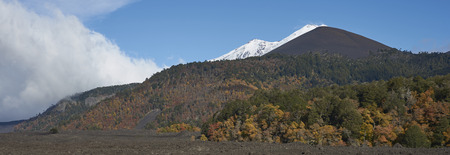 Snow capped peak of Volcano Llaima (3125 meters) rising above the lava fields and forests of Conguillio National Park in the Araucania region of southern Chile