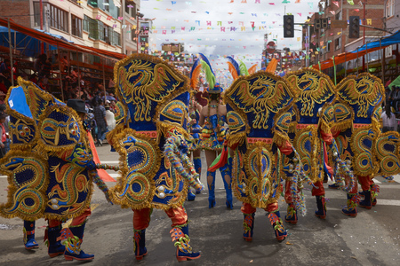 ORURO, BOLIVIA - FEBRUARY 26, 2017: Masked Morenada dancers in ornate costumes parading through the mining city of Oruro on the Altiplano of Bolivia during the annual carnival Editorial