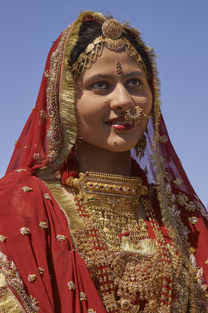 Jaisalmer, Rajasthan, India - February 19, 2008: Indian lady dressed in ornate red sari and adorned with traditional Indian jewellery at the annual Desert Festival in Jaisalmer.