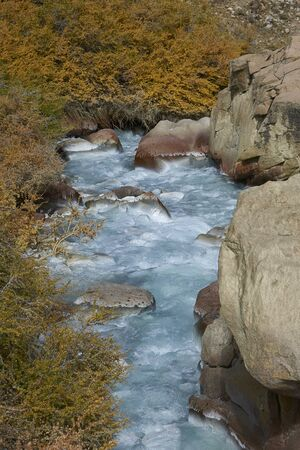 Ice cold river from the Paloma glacier running through autumn coloured vegetation in the Yerba Loca Mountain Park near Santiago in Chile