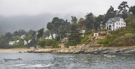 ZAPALLAR, CHILE - MAY 9, 2014: Houses snuggle around the coast in the peaceful town of Zapallar on the coast of central Chile.