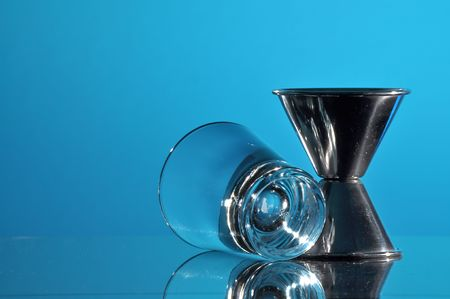 Bartenders Jigger and Shot Glass on blue