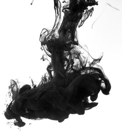 Tinta de Indias en agua con un fondo blanco de la espalda.  Foto de archivo