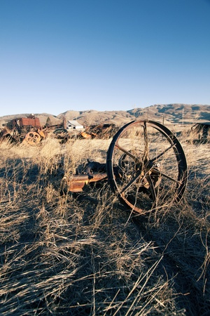old rusty farm equipment in the middle of a field Stock Photo - 9894958