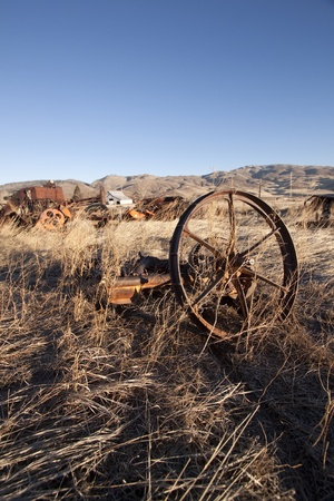 old rusty farm equipment in the middle of a field photo