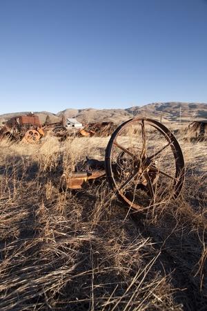oude roestige landbouwmachines in het midden van een veld
