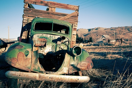 An old abandoned vintage delivery truck van in a field Stock Photo