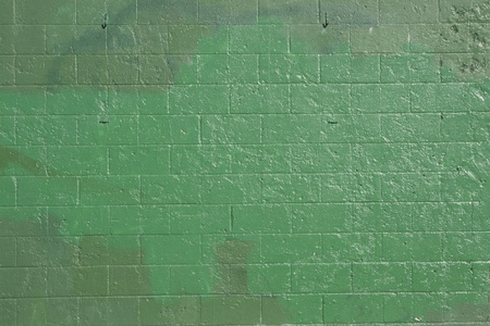 green brick wall that has been covered up with off shades of green to cover grafitti. photo