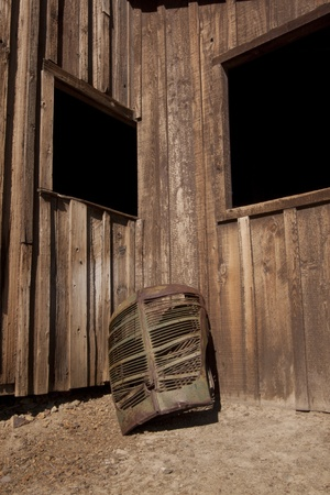 A rusty old truck grill against a barn.