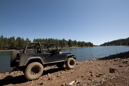 a close up of offroad vehicle in the dirt. with a lake in the background photo