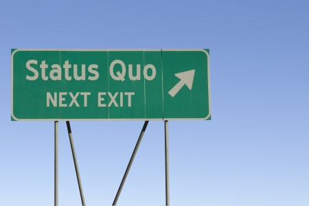 quo: Green road sign with a blue sky gradient background.