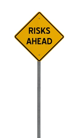 risks ahead: a yellow road sign with the words RISKS AHEAD on white background Stock Photo