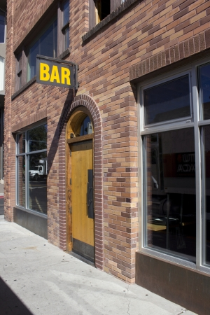 a brick building with a bar sign over a wood door. photo