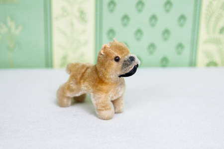 plushie: old brown plushie dog with a black nose