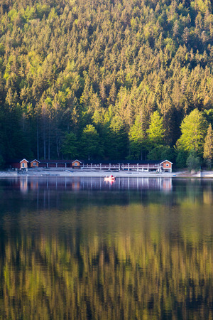 Boat and Boathouse in the early morning on a german alpine lake.