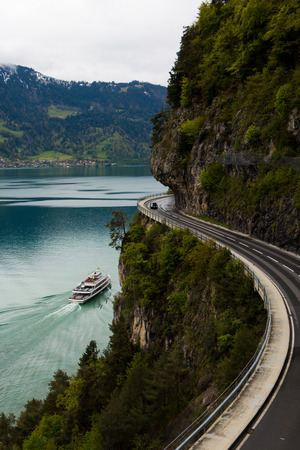 Winding mountain road at lake Thun in Switzerland with a boat passing by, car on the road