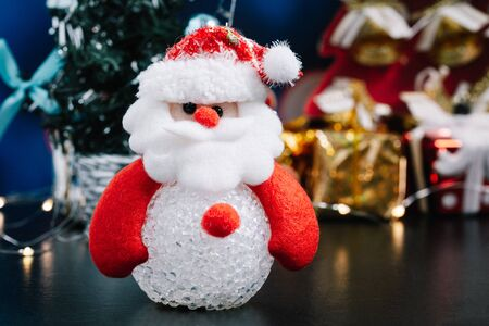 Close-up of Santa in foreground, Christmas Holiday Season background with decorations. Merry Christmas New Year collection, gifts and decorative ornaments. Empty copy space for text. Zdjęcie Seryjne