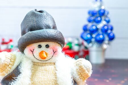 Close-up of snowman in foreground, Christmas Holiday Season background with decorations. Merry Christmas New Year collection, gifts and decorative ornaments. Empty copy space for text.